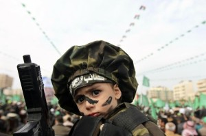 A boy wearing an Al-Qassam Brigades headband is carried by his father during a Hamas rally in Gaza City