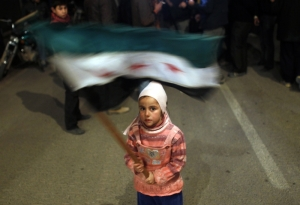 A girl waves a Syrian opposition flag during a protest against President Bashar al-Assad, February 27, 2012. (Goran Tomasevic/Courtesy Reuters)